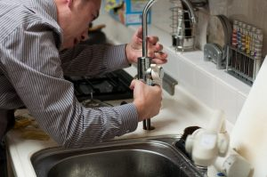 plumber fixing sink faucet